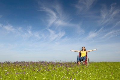 joyful woman using wheelchair in field of flowers